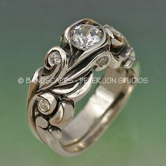 This ring is deeply carved with scrolls that curl into settings for the small stones, as well as the large center. The side stones are each 2mm and weigh .03ct. There are six of these total - and please detect the two that are set vertically on the side wall, under the center stone. Because there is a beautiful elegance to this part of the wedding set, I made a very simple and narrow shadow band to go along with the engagement ring. This band fits very tight, is complimentary, and does not…
