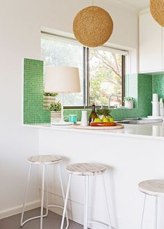 Jules has lifted the white kitchen with natural woven pendants and a green mosaic splashback.