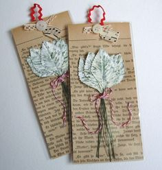 Painted and distressed leaves tied together with red and white bakers twine packaged with a vintage German book page, shell button and snippet of lace