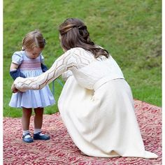 |September 28, 2016|  Catherine, Duchess of Cambridge helps her daughter, Charlotte with her cardigan. Garden Party, Vancouver Canada.  9/29/2016.