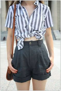 Trendy woman in gray high-waisted shorts and striped shirt