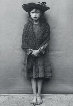 U.K. Adelaide Springett was so ashamed of her tattered boots, she took them off for this 1901 photograph. Adapted from Spitalfields Nippers by Horace Warner.