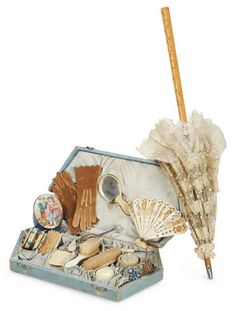 "French Accessories for Bebes 16"" (41 cm.) parasol. Including a wooden-handled parasol covered with alternating bands of aqua silk ribbon and embroidered tulle, with lace ruffle. Along with a fitted box with silk lining containing various carved bone combs, brushes, shoehorn, and powder jar with puff, along with an enamel glass bottle, kidskin gloves, and a fretwork-carved folding fan. French, late 1800s."