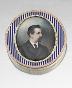 IVORY AND ENAMEL PHOTOGRAPH FRAME, CARTIER, CIRCA 1900.  Centring on an oval glass compartment bordered by white enamel bead work motifs, to an outer frame accented with lines of blue and white enamel, to an ivory back, measurements approximately 75mm x 76mm x 12mm, signed Cartier Paris, French assay marks, ivory damaged.