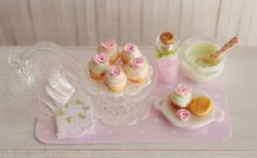 Miniature Cupcakes With Lt. Green Icing, Pink Roses And Sugar Sprinkles, Covered Glass Cake Stand, Bowl Of Icing, Pink Sugar, And Tea Towel on Etsy, $32.50