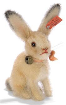 A STEIFF SMALL HEAD-TURNING RABBIT, (3310 H), light brown mohair, wool plush face, ears and tail, brown and black glass eyes, red stitching, whiskers, tail-operated head-turning mechanism, ribbon with bell and FF button with red cloth tag, circa 1932 --4in. (10cm.) high