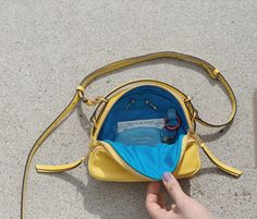 Hand-crafted 4 in 1 small sunrise bag is made to ride different waves throughout our changing day. Real 18 Karat Gold Plated custom designed hardware gives extra sunrise glow. Front compartment has built in phone, lipstick and pen slots. Main compartment has 1 slash pocket with 2 credit card slots and a red floating key ring. On-the-go metro card slot at center back. 4 In 1, Blue Line, Dark Denim, Cowhide Leather, Sunrise, Shoulder Bag, Slot, Waves, Hardware