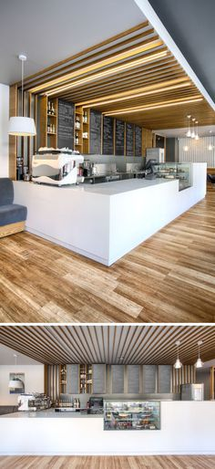 This cafe service counter mixes white counters with glass, wood detailing and chalkboards. Hidden lighting runs overhead along the the wooden details.