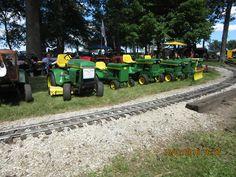 John Deere  garden tractors line up near train tracks