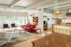 open plan living area with red coach and mid century chairs
