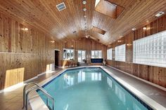 All wood interior pool with tile deck wrapping around the pool.  Ceiling contains skylights for additional natural light.