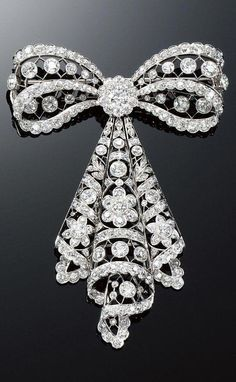 DIAMOND BROOCH 1910s. In the garland style designed as an articulated tied ribbon decorated with stylised floral motifs millegrain- and collet-set with circular- and single-cut diamonds. #diamondbrooch