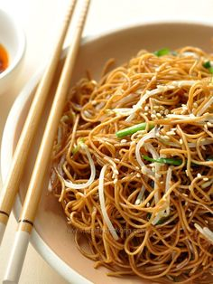 Cutlery propped on a plate of noodles in a white bowl