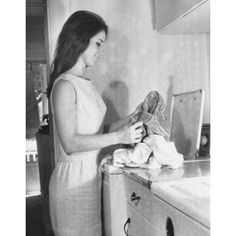 Side profile of a young woman putting clothes into a washing machine Canvas Art - (18 x 24)