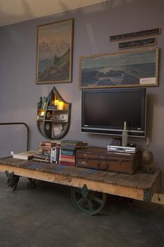 Ideas For Creating Upcycled Tables, Desks and Workstations: This old factory cart, with its run-down appearance and painted wheels is transformed into a unique entertainment center.   From DIYnetwork.com