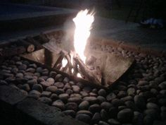 DIY fire pit - I used an old oil drum braai / BBQ, buried it into an old built plant box with river sand around and put river stones on the top. Works wonderfully and looks great too.