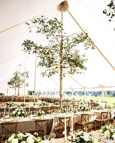 Outdoor dinner party underneath a large white tent