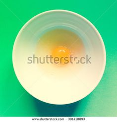 egg in a bowl on multicolored background, minimal design, direct flash - stock photo