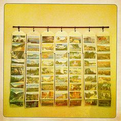 Vintage postcard display using a curtain rod, rings, and clamps from Lowe's.