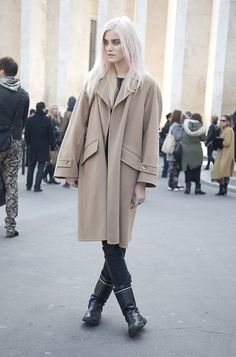 Barely pink hair and an oversized camel coat with black CHANEL boots.