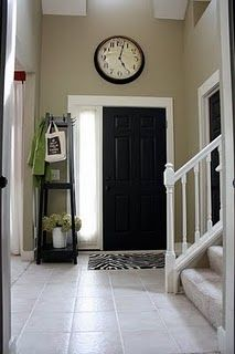 I love this entry.  It inspired me to paint my main living area tan, my trim white and soon to be black door.  I also tried hanging a small clock above the door, but it just fell and broke ;0( sad day for me.