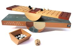 """""""In March 2012, the Marbles Game Design Contest was won by Matt Buchanan with his idea aptly named Rock Me Archimedes. By combining strategy, skill, and a little bit of luck, the game consists of a wooden board that rocks like a teeter-totter, a special die, and 28 marbles. To win, you need to be the first player to oh-so-carefully get four marbles to your end of the board without causing it to touch the table."""""""