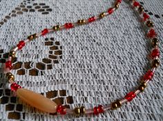 This tasty treat is all handmade with pretty pink bugle beads as well as gold and red glass beads and is centered by a caramel color pipe bead! Secured by a Lobster clasp  Size - 18""