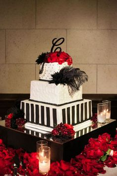 A glam black and white wedding cake adorned with black feathers and red roses.