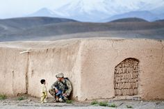 Sgt. Joshua Smith, a paratrooper with the 82nd Airborne Division's 1st Brigade Combat Team, chats with an Afghan boy during an Afghan-led clearing operation April 28, 2012, Ghazni province, Afghani...