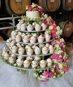 White wedding cupcake tower with cascading flowers at the side #wedding #cupcakes #cupcaketower #white #weddingcupcakes