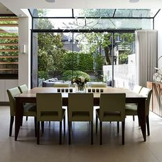 Open plan dining room with glass doors This light-filled dining room has full height glazed doors that open on to a contemporary garden seating area.