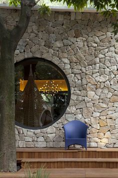 How stunning is this large round window set in a stone faced wall?
