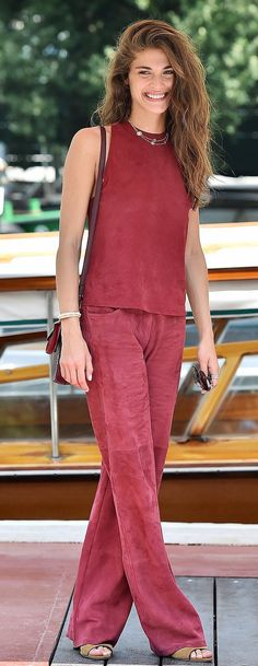 Elisa Sednaoui in a red silk Trussardi pants and top ensemble with nude sandals