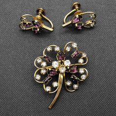 "Vintage Star-Art Flower Brooch Earrings Purple Rhinestone Gold Filled  Vintage signed Star-Art 1/20 12k gold filled brooch earring demi set. Delicate blooms are accented with purple amethyst and rhinestone baguettes and chatons. Maker: Star-Art Material: glass Approximate Size: Brooch measures approx. 1 1/2"" x 1 3/4""; earrings measure about 1"" Condition: very good, pre-owned Your purchase will be shipped in an attractive jewelry gift box.    #FeedCondUsed #BroochesAndPins…"