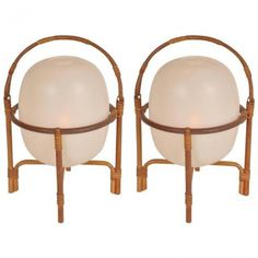 This pair of Cestita lamps was designed by Miguel Milá and manufactured by Tramo in Spain in 1962. The lamps have bamboo structures with round handles that can be put in two positions. These bases hold plastic shades, allowing the lamps to emit a warm light. The use of materials creates a contrast, especially when lit. They remain in good original condition, with minor wear consistent with age and use, preserving a patina.