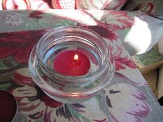 Take lid from a yankee candle,  remove the plastic seal with a screw driver, then use as a tea light holder for your home or porch.  Great idea.
