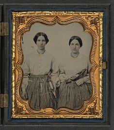 Lucretia and Louisa Crossett, dressed alike holding weaving shuttles, light colored blouses with strange print skirts.