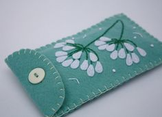 Handmade felt case for phone, i pod, gadget. 7cm x 15cm / 2.75 x 5.25 inches Appliqued and embroidered agapanthus flowers, blanket-stitched edges, contrasting lining and a button fastening. Size (excluding stitched edges) 7cm x 15cm / 2.75 x 5.25 inches Duckegg background with light cream lining. Please see separate listings for other colours