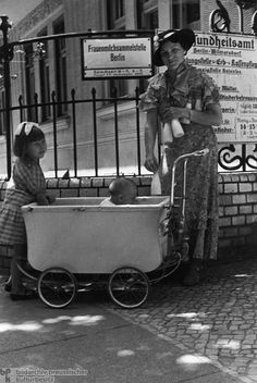 "Woman with Two Children in Front of the Breast Milk Collection Site of the Health Office in Berlin-Wilmersdorf (1936) Breast milk distribution was just one of the many services offered to ""desirable"" members of the population. The sign behind the mother, however, points to the other types of ""services"" provided by these public health offices: it reads ""Counseling Center for the Care of Heredity and Race."""