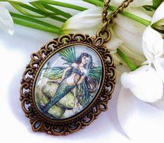 Halskette im Vintage-Stil mit schönem Meerjungfrau-Motiv.  Die Kette besteht aus einer antikgoldfarbenen Metallfassung und einem handgearbeiteten Glas