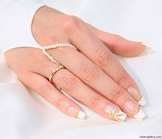 Bride wearing gold nail art over French Manicure with 3D flower: You can dress up one fingernail with 3D nail art and lightly paint it and your other nails. Wearing a gold wedding ring? How about a light dusting of gold on your French Manicure? Try something old (French) with something new (art). Diagonal French wedding manicure with gold glitter and one rhinestone.