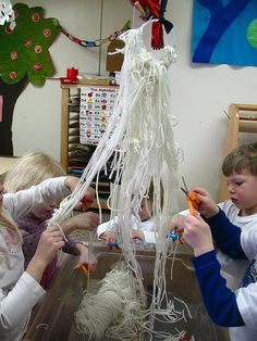 Cutting yarn is a wonderful activity to build up those hand muscles used for writing...but it's so tricky for little ones to do! Suspending it from the ceiling so they can pull and cut, is a great idea!