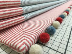 Stripes are perfect for Romans with horizontal contrast bands & pompom trim. Handmade in Bedfordshire by Denton Drapes.