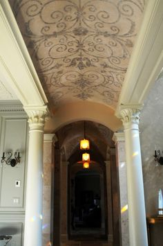 An ornate stone barrel vault turns into a groin vault further down the hallway. Two stone pillars stand on either side of the hallway.