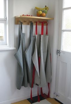 No4 House Apron and No3 House Aprons. https://folksy.com/shops/adoglikesparky. Printed gingham linen-look cotton crossover back apron and cotton ticking apron with red ties.