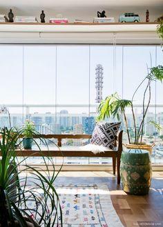 Varanda com banco de madeira antigo, tapete étnico, garden seat e vasos com plantas.