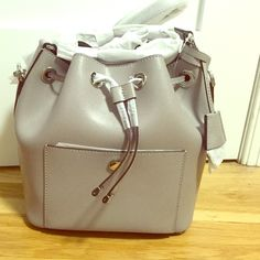 Michael Kors Greenwich Bucket Bag Brand new, never been used Michael Kors leather bucket bag. Great for day to day or nighttime! Has shoulder strap and inside pockets. Fastens with magnetic clasp. Comes with purse bag as well. Bucket bags are very trendy for Spring/Summer and this nice gray color goes with any outfit! Michael Kors Bags Shoulder Bags