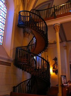 Loretto Chapel~Santa Fe, NM. The legend has it that the sisters of Loretto had no stairway to reach the choirloft of their new chapel and then one day a mysterious carpenter appeared from the desert and proceeded to build a spiral staircase. No nails in the stairway & No center support. Carpenter disappeared as he had come, without anyone knowing him or payment him. The railing is a relatively recent addition (about 100 years), because the sisters were afraid when climbing them without a…