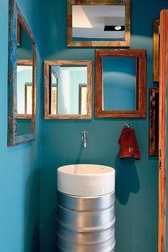 Pia foi feita com dois barris de chope e uma cuba. Ligada direto à parede, a torneira de jardim dá um ar rústico ao espaço, que tem espelhos com moldura de madeira de demolição