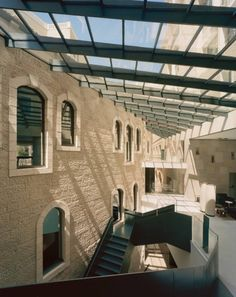 Inside the hotel a paired-back, minimalist aesthetic contextualizes and frames the historic Jerusalem architecture. Traditional rough-faced running-bond masonry walls meet walls of the same material rendered in large, smooth blocks. By contrast, a bold, sculptural metal staircase moves through the skylit central atria between concrete floors.